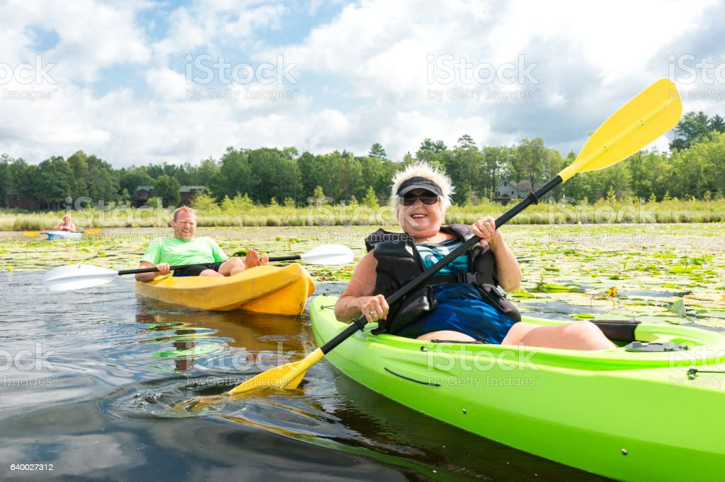 Mom and grown kids kayaking stock photo