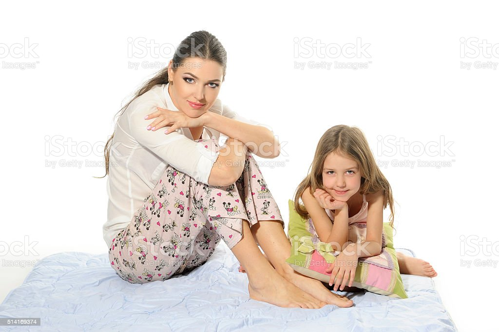 Mom and her daughter, blue blanket, pajamas. stock photo
