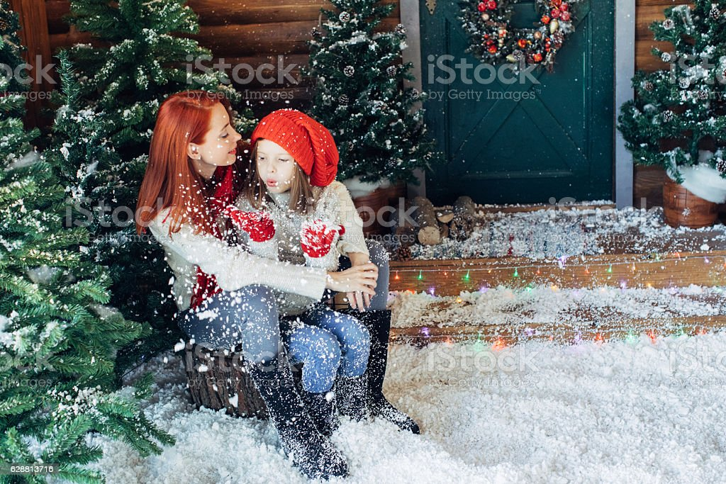 Mom and her daughter playing with snow stock photo