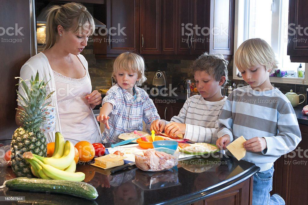 Mom and her three sons making healthy lunch in kitchen. stock photo