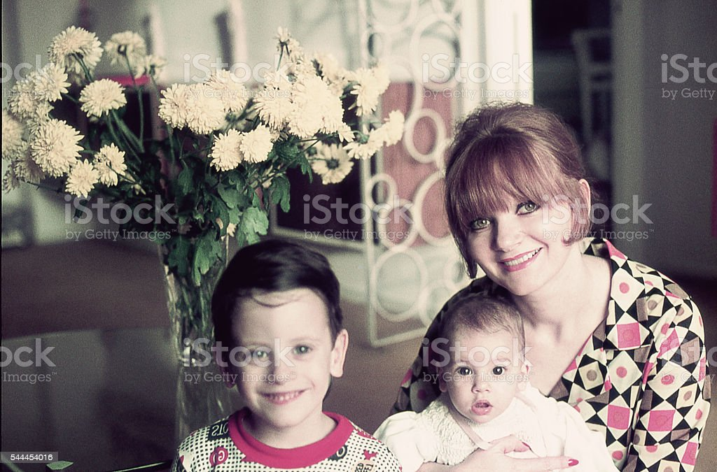 Mom and her two children at the living room stock photo