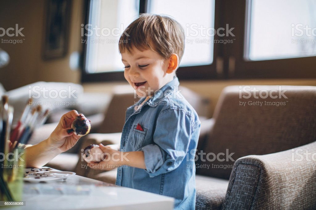 Mom And Kid Having Fun Dyeing Eggs stock photo