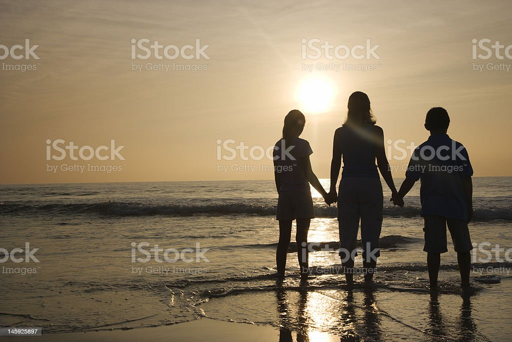 Mom and kids at beach. stock photo