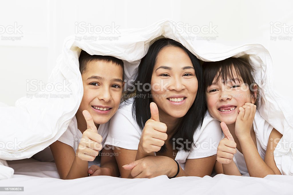 Mom and kids laying in bed giving thumbs up royalty-free stock photo