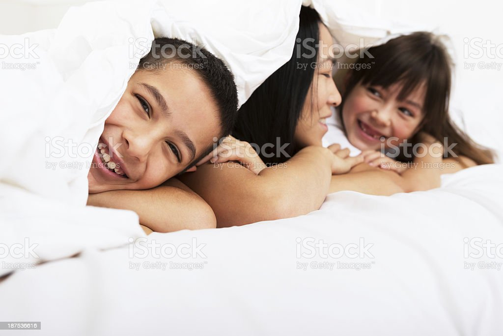 Mom and kids laying in bed royalty-free stock photo