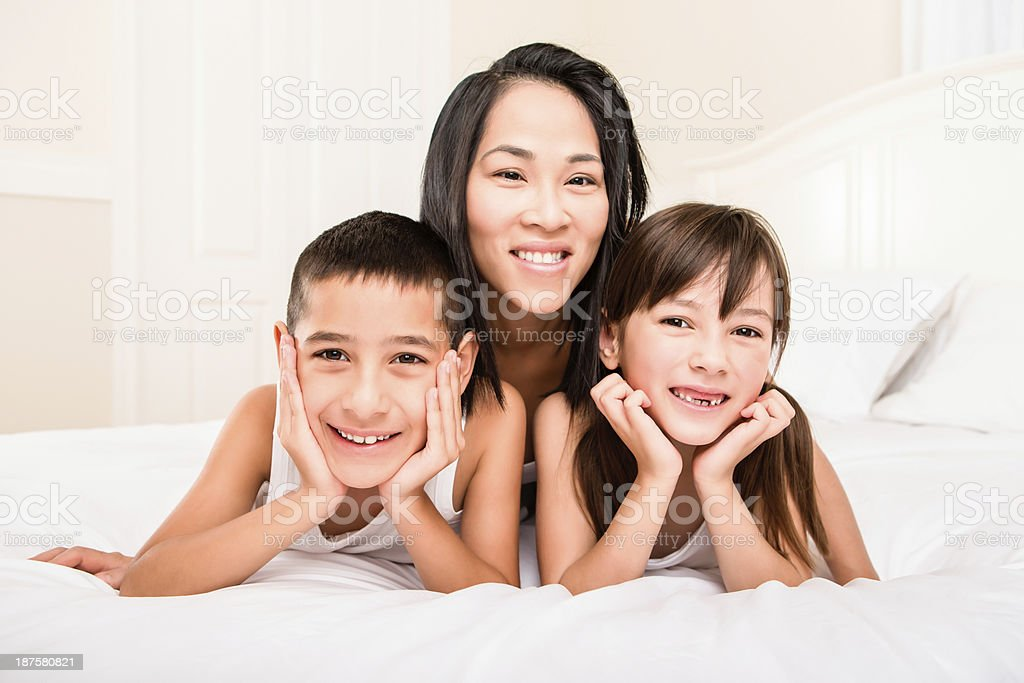 Mom and kids laying on the bed royalty-free stock photo