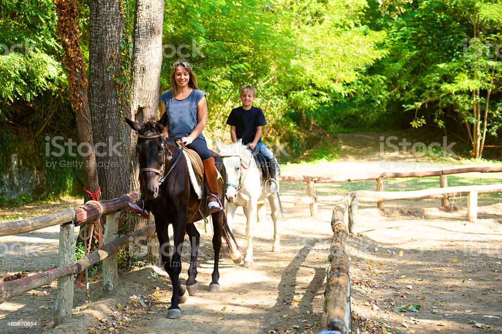 Mom and son go horse riding stock photo