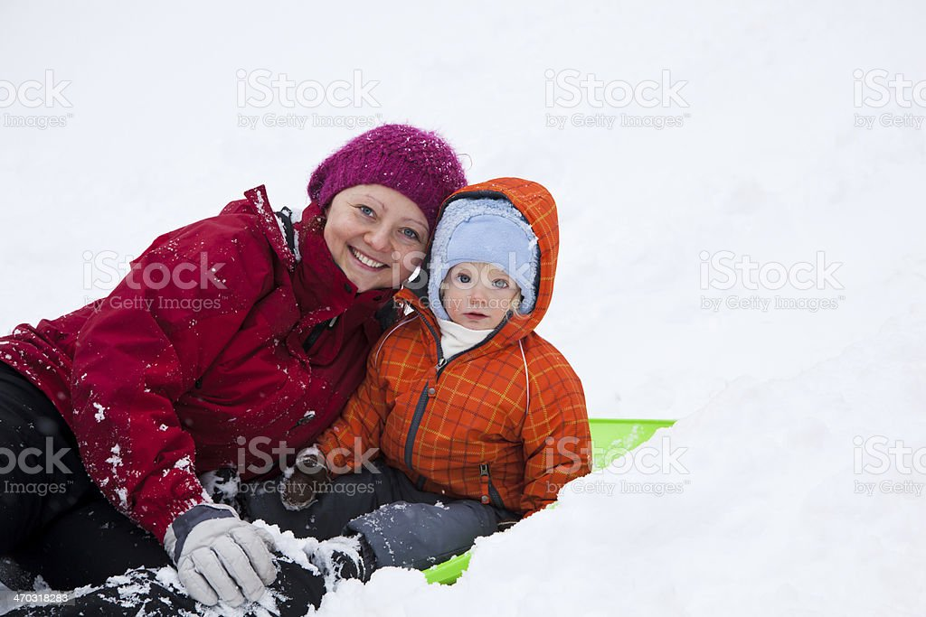 Mom and son play on snow stock photo