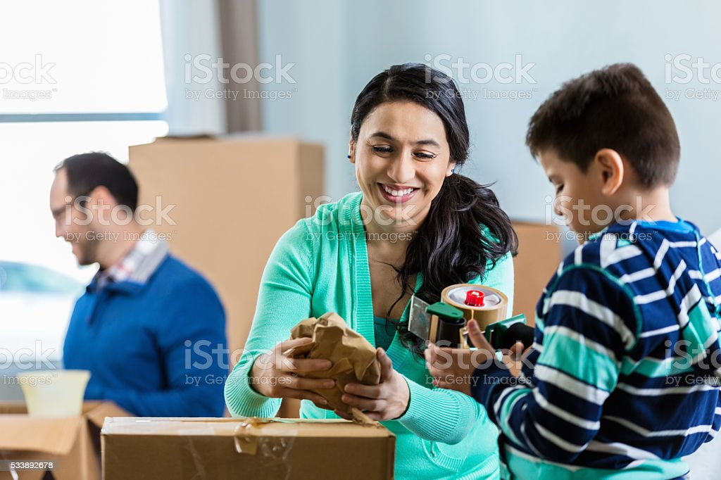 Mom and son prepare box to be moved stock photo