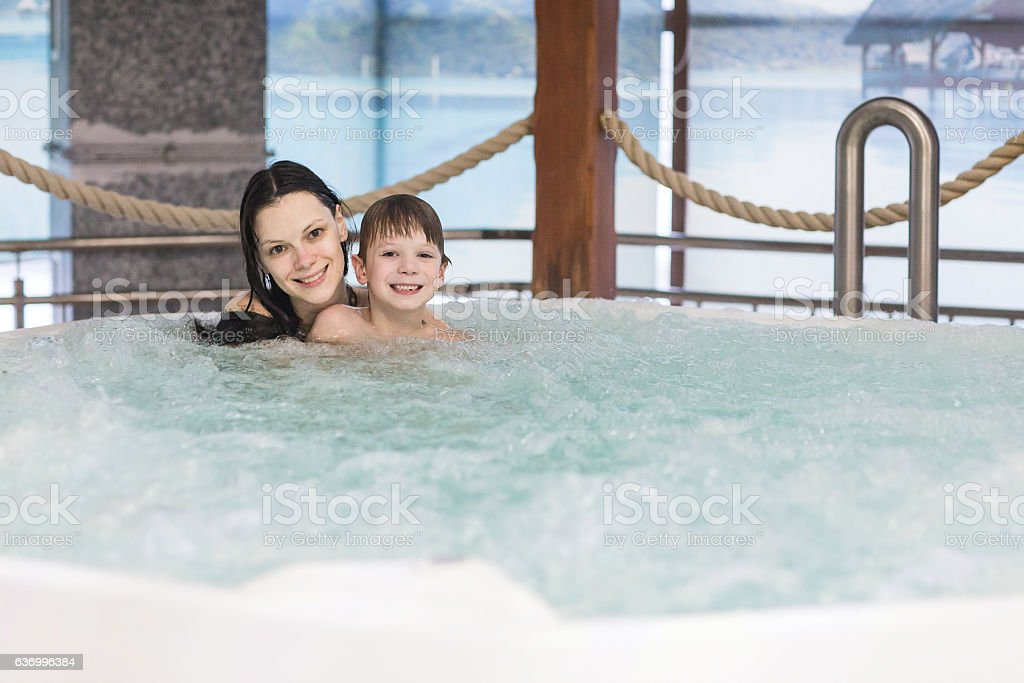Mom and son relax in the tub stock photo