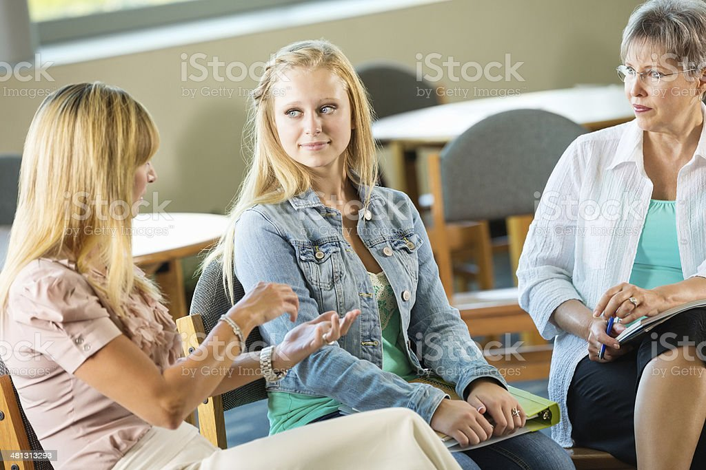Mom and teen daughter meeting with school counselor stock photo