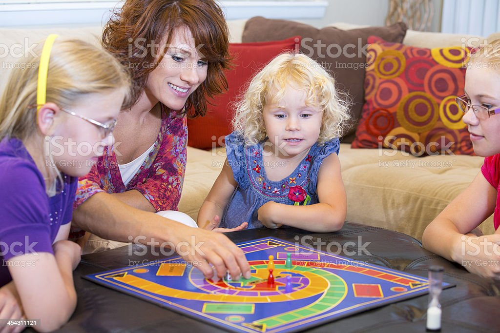 Mom and three kids playing an exciting board game stock photo