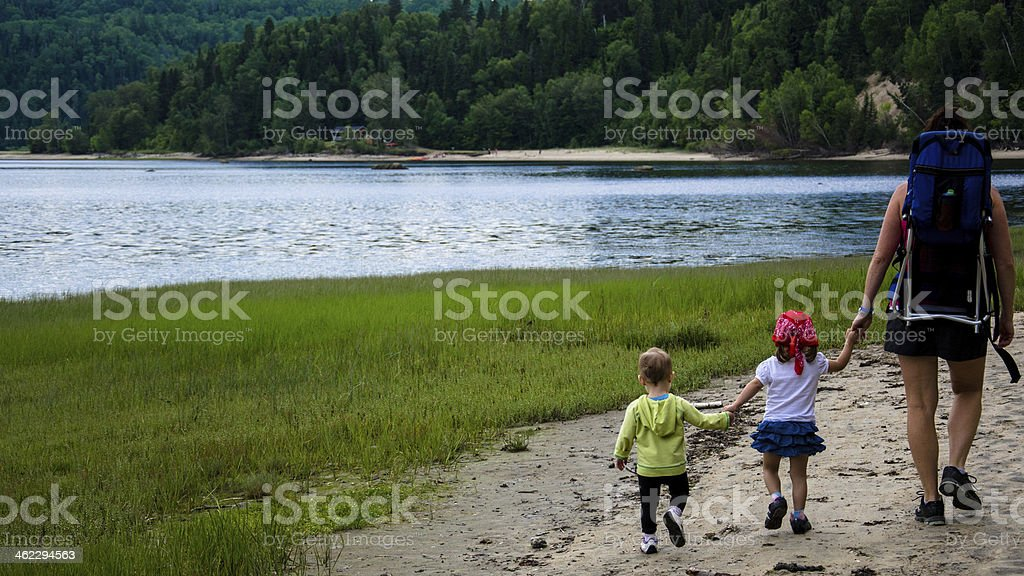 Mom and two baby walking on the beach holding hands royalty-free stock photo