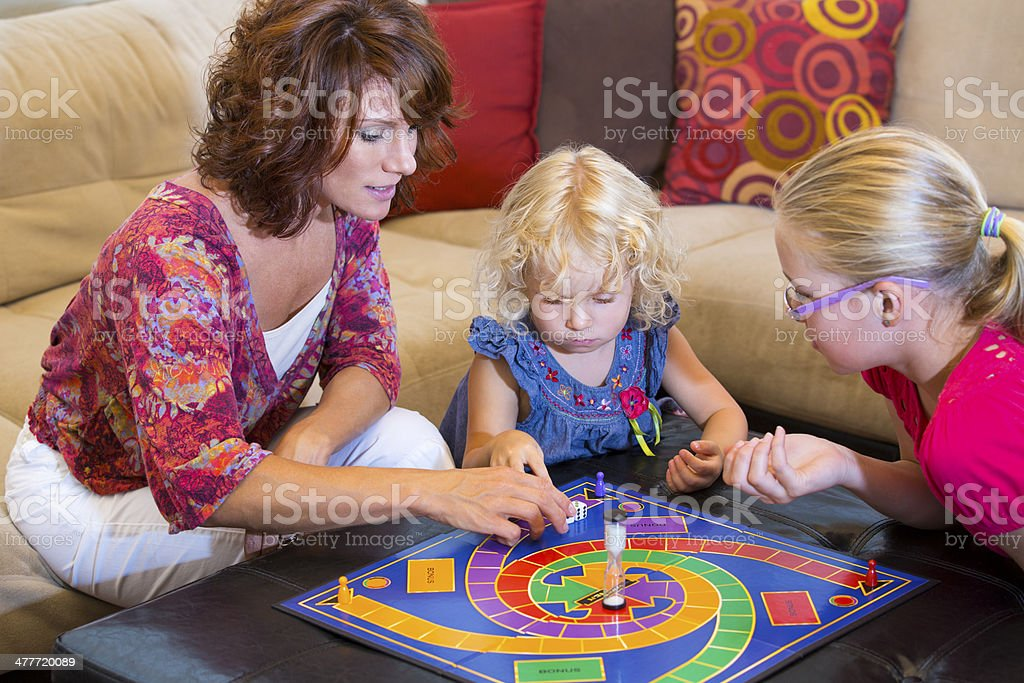 Mom and two kids playing a board game at home stock photo