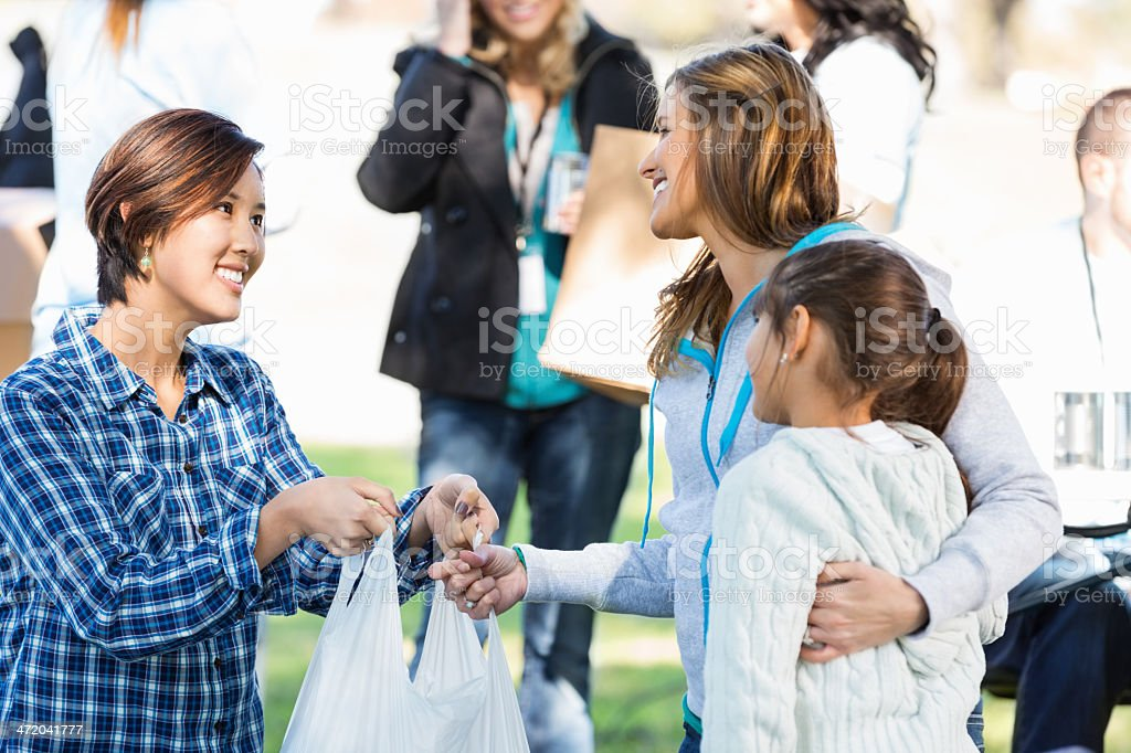 Mom and young daughter accepting donations at food/clothing drive stock photo