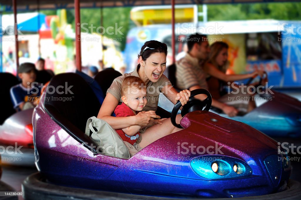 Mom and young son in a bumper car at an amusement park stock photo