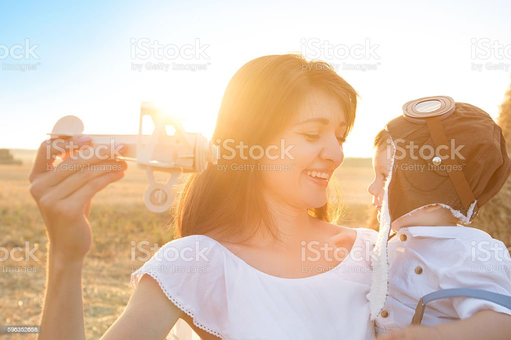 Mom and young son playing with a toy airplane. stock photo
