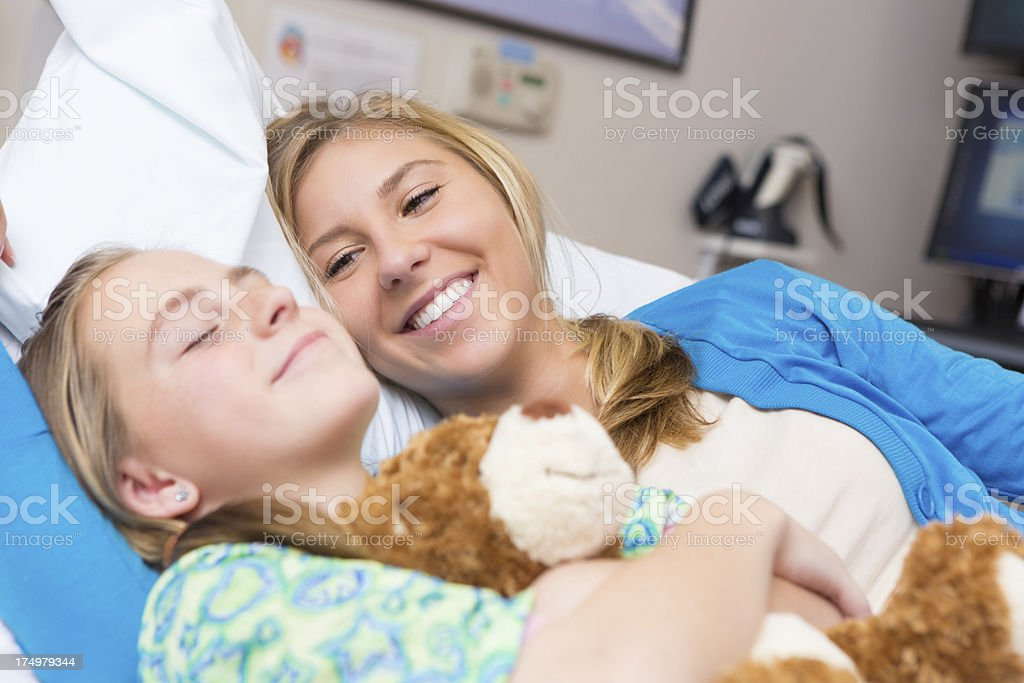 Mom cheering up sick daughter in hospital room royalty-free stock photo