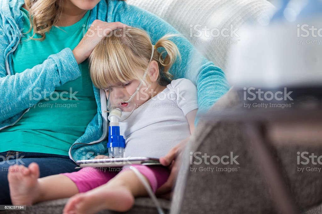 Mom comforts daughter receiving breathing treatment stock photo