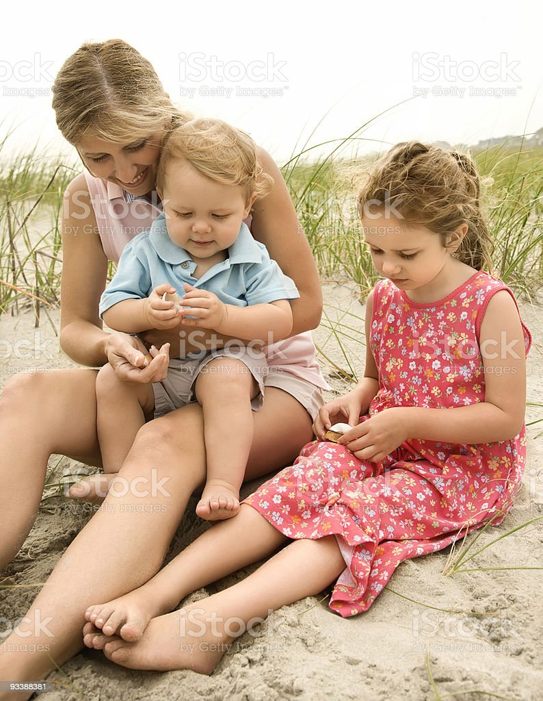 Mom, daughter and son looking at shells. royalty-free stock photo