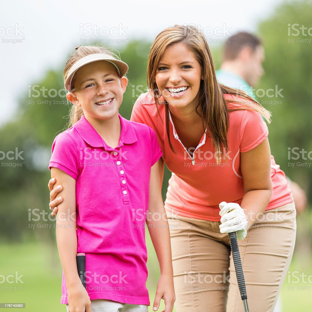 Mom & daughter playing golf together on course stock photo