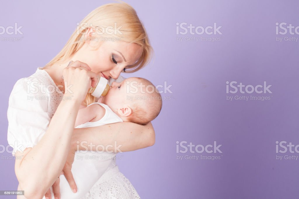 mom feeds the baby from the bottle with teat stock photo
