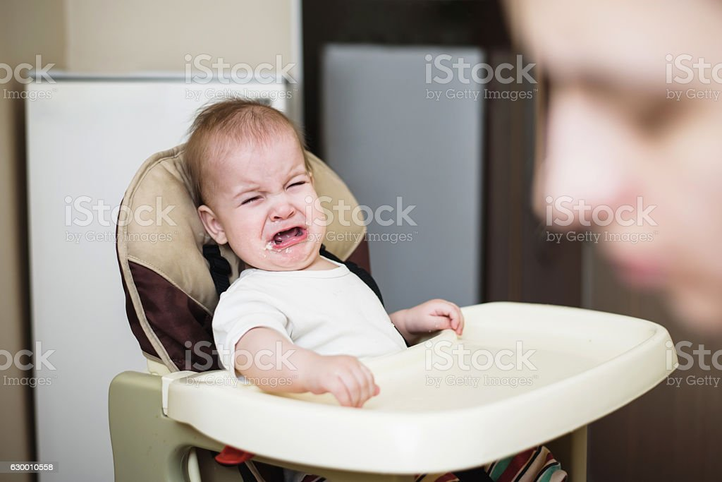 Mom feeds the baby who is naughty stock photo