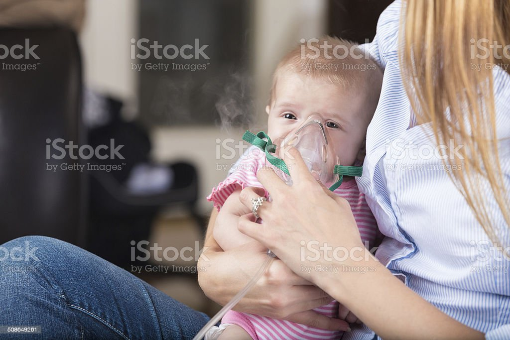 Mom giving nebulizer breathing treatment to sick infant baby stock photo