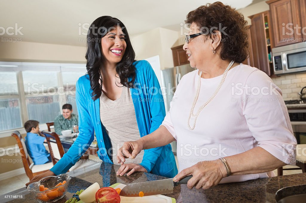 Mom & grandmother preparing dinner for family in kitchen royalty-free stock photo