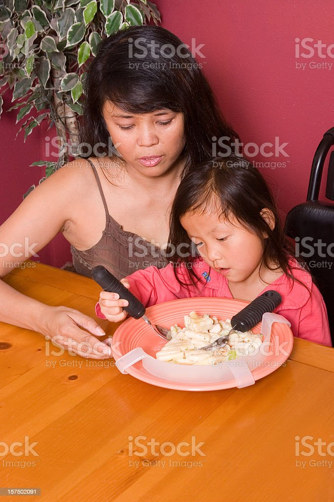 Mom helping daughter with adaptive silverware royalty-free stock photo