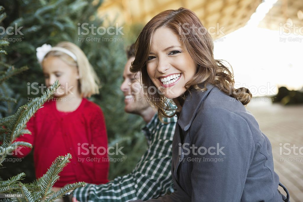 Mom helping family chioose Christmas tree to buy royalty-free stock photo