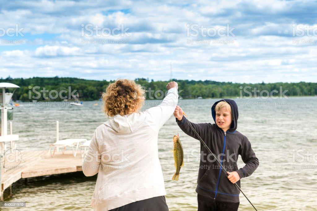 Mom helps son fishing stock photo
