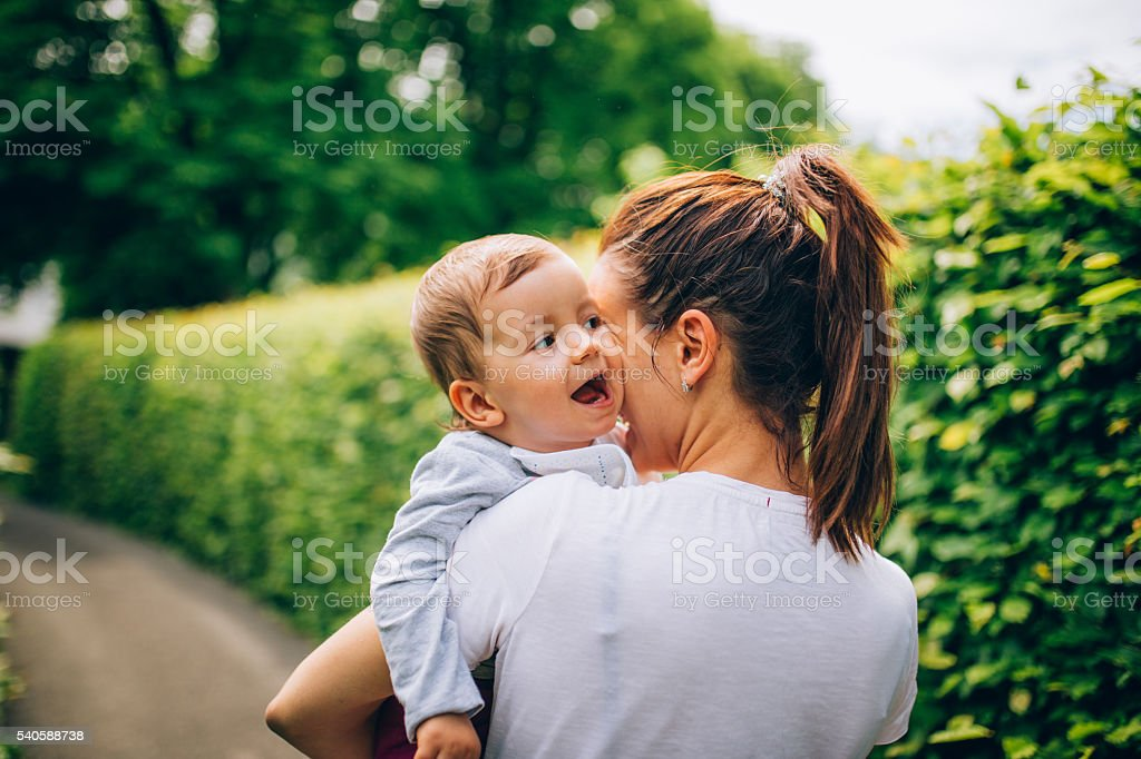 Mom holding child in park stock photo