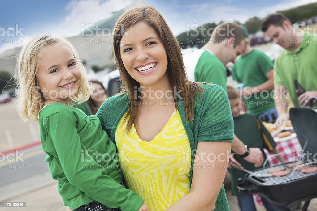 Mom holding daughter at tailgate party sports event royalty-free stock photo