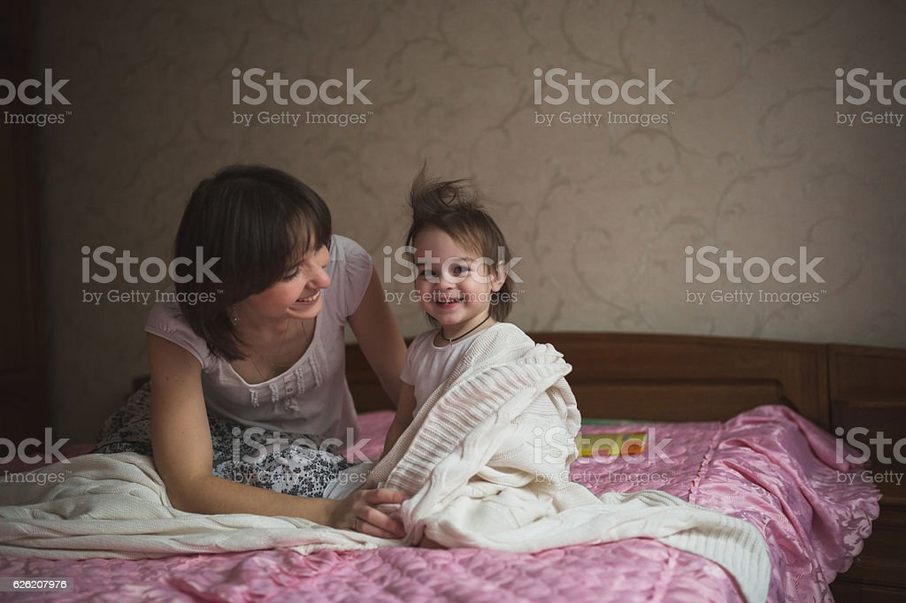 Mom hugs and plays with her daughter hide and seek stock photo