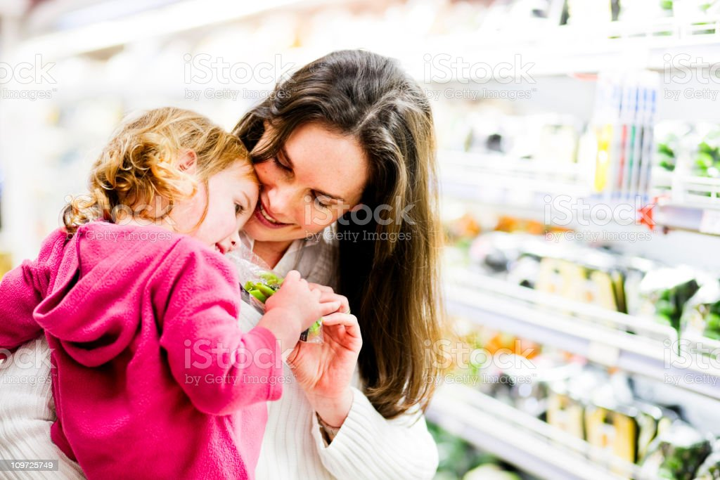 Mom hugs daughter in supermarket royalty-free stock photo