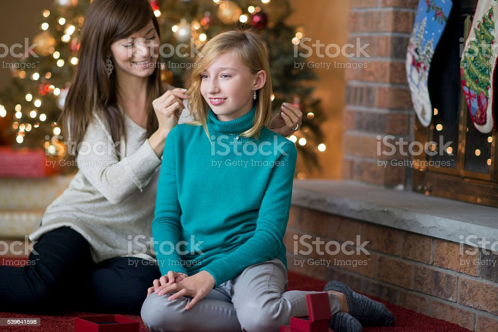 Mom is putting a necklace on her daughter while stock photo