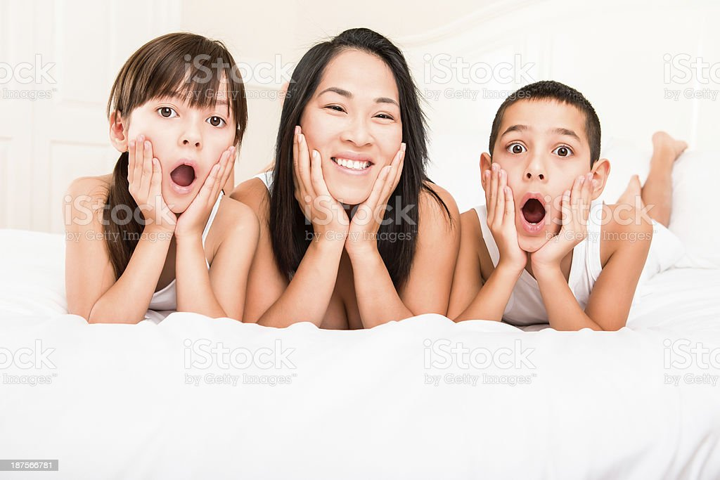 Mom laying in bed with 2 surprised kids royalty-free stock photo