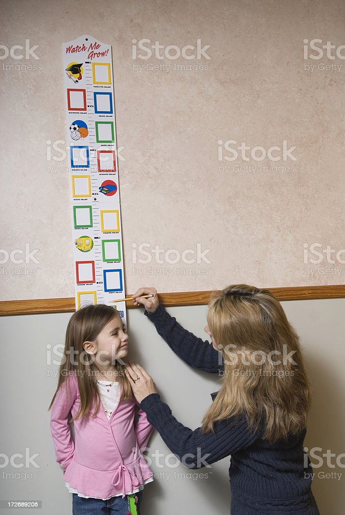 Mom measuring the growth of her daughter. stock photo