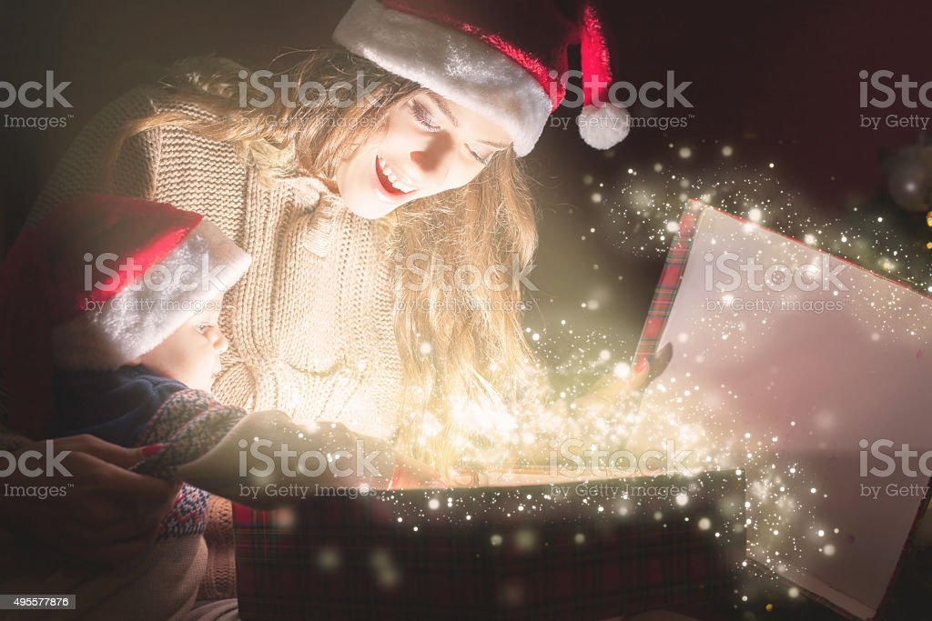Mom opens the magic box with a gift for child stock photo