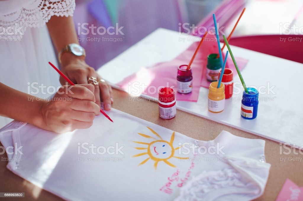 Mom painting baby cloth for her baby girl. stock photo