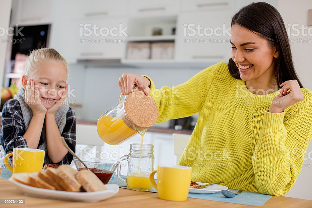 Mom pouring orange juice into a glass stock photo