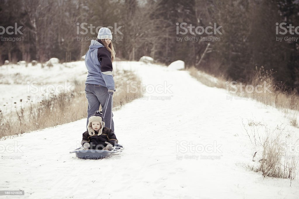 Mom pulling boy in sled stock photo