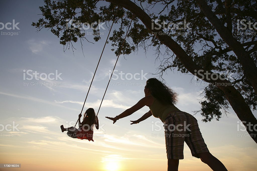 Mom pushes Daughter on swing set playing at sunset  silhouette stock photo