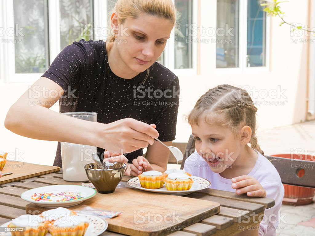 Mom puts confectionery glaze spoon on Easter cupcake stock photo
