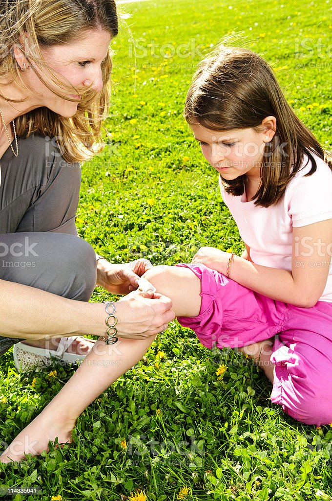 Mom putting a bandaid on her daughter's knee stock photo