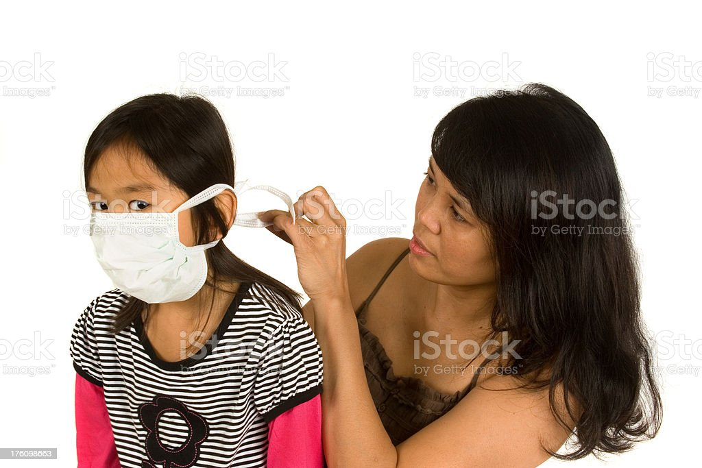 Mom putting mask on little girl royalty-free stock photo