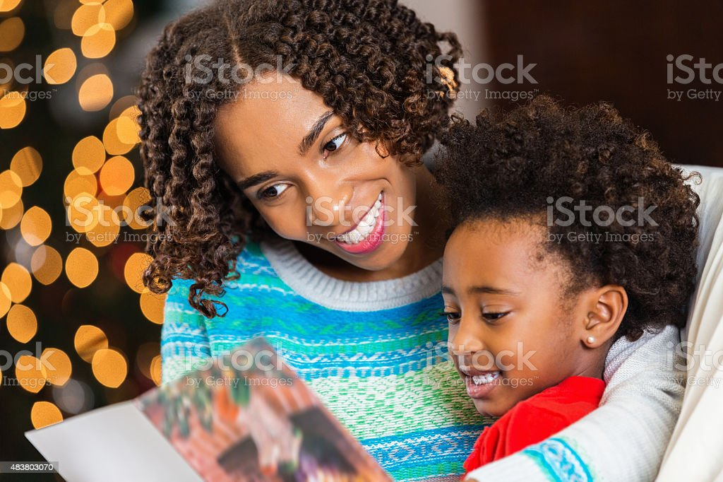 Mom reading Christmas card to daughter at home stock photo