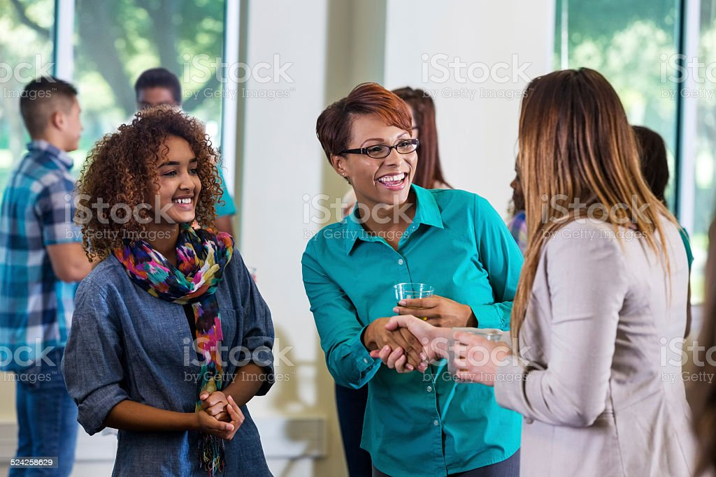 Mom shaking hands with daughter's teacher during school event stock photo