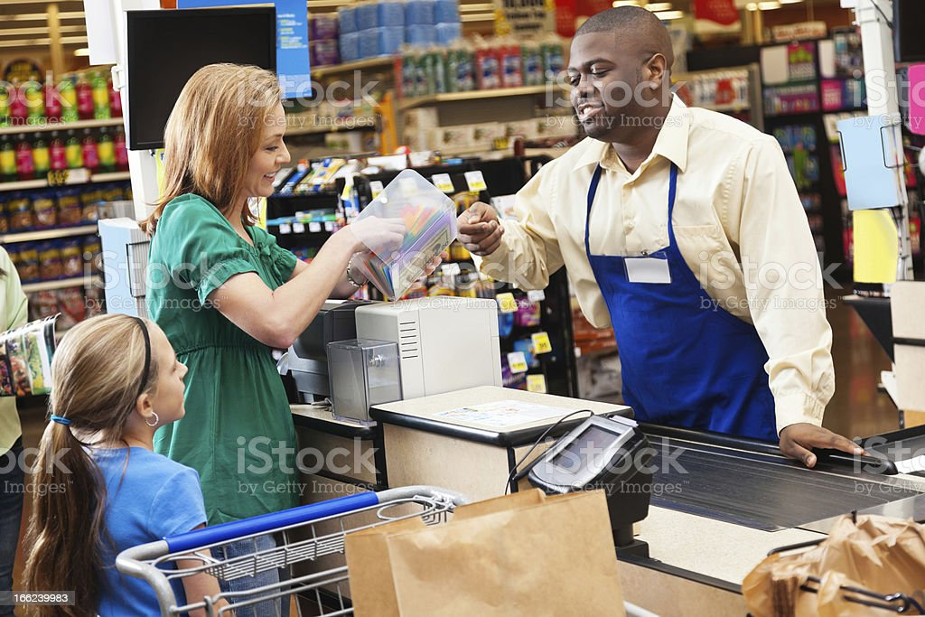 Mom shopping for groceries with daughter, checking price on item stock photo